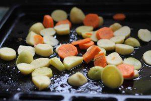 Порезанный картофель и морковка на противне