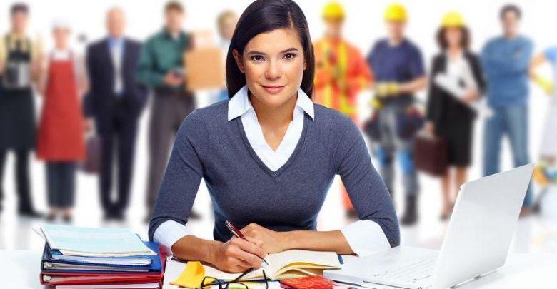 Девушка на белом фоне сидит за столом вместе с папками и улыбается