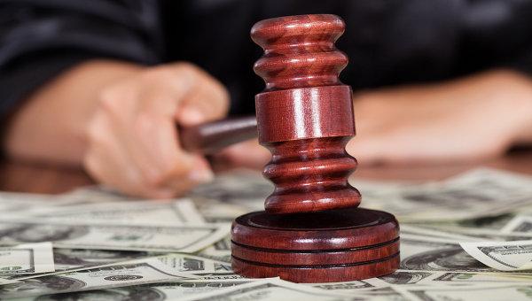 Молоток судьи и доллары разбросанные по столу