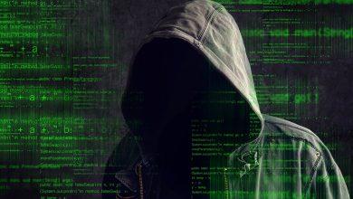 человек в темном помещении в копюшоне на фоне зелёной таблицы