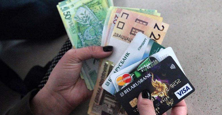 Женщина держит деньги и карточки
