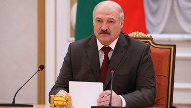Лукашенко сидит за столом с бумагой и микрофоном