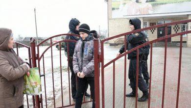 Подозреваемый в наручниках покидает здание школы №2 в Столбцах
