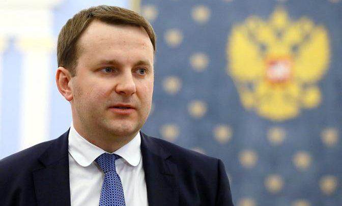 Максим Орешкин Минэконом развития России на фоне Российского Герба