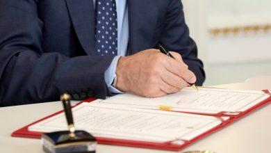 высокопоставленный чиновник подписывает документ