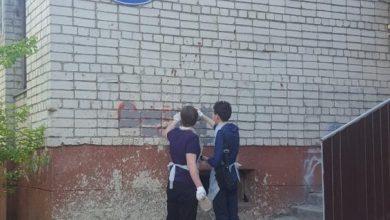 Два человека закрашивают надписи на стенах