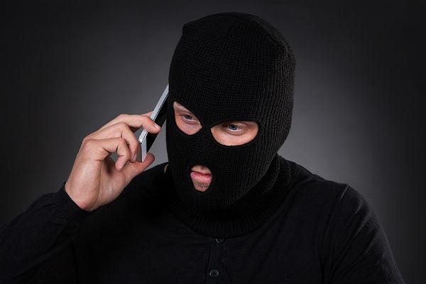 Человек в маске говорит по телефону