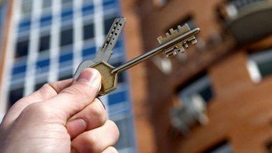 Человек держит ключи на фоне жилого дома