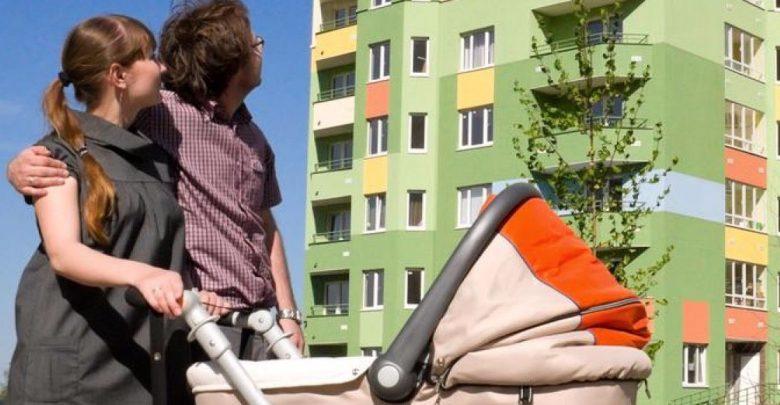 Пара с коляской смотрит на жилой многоквартирный дом