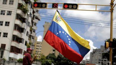 мужчина держит в руках флаг Венесуэлы