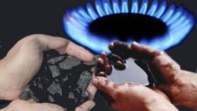 Руки держат нефть и уголь на фоне горящей газовой комфорки