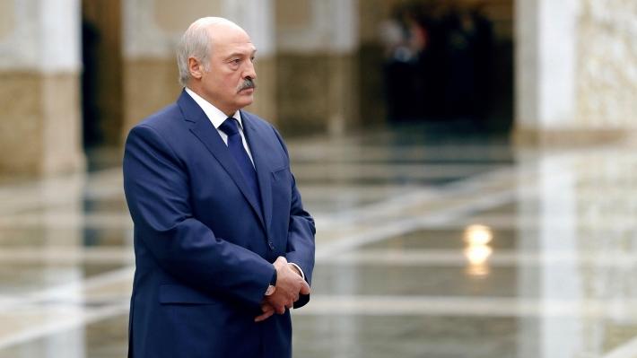 Александр Лукашенко стоит взале сведя руки