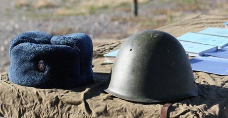 Военная каска и шапка ушанка на лежат на столе