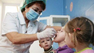 Женщина врач осматривает детей