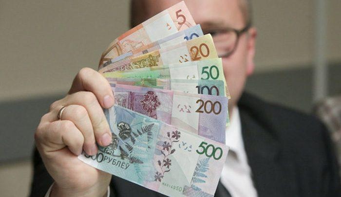 Человек держит в руке различные купюры Белорусского образца