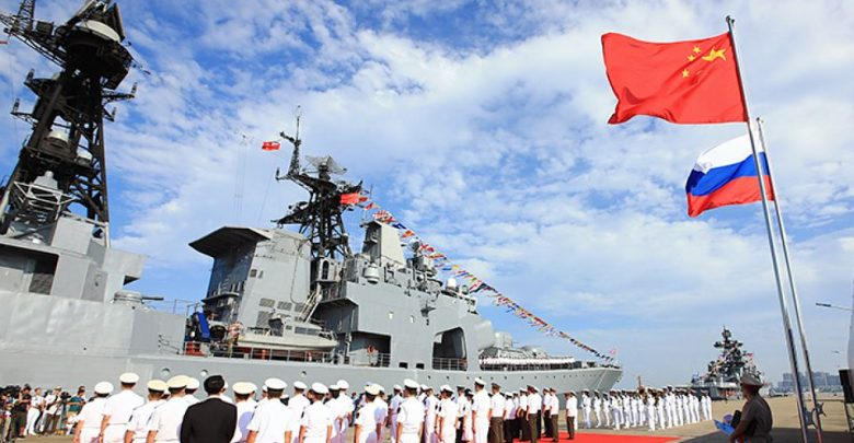 Моряки из Росссии и Китая на фоне военного корадля и флагов двух стран