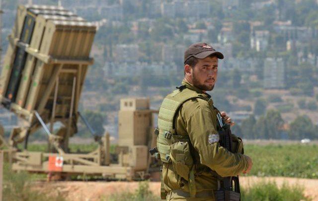 Солдат арми обороны Израиля охраняет противоракетную систему Железный купол