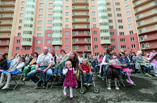 Множество семей с детьми во дворе дома