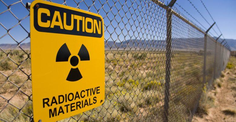 Предупреждение о радиации на английском языке на сетчатом заборе в пустынной местности