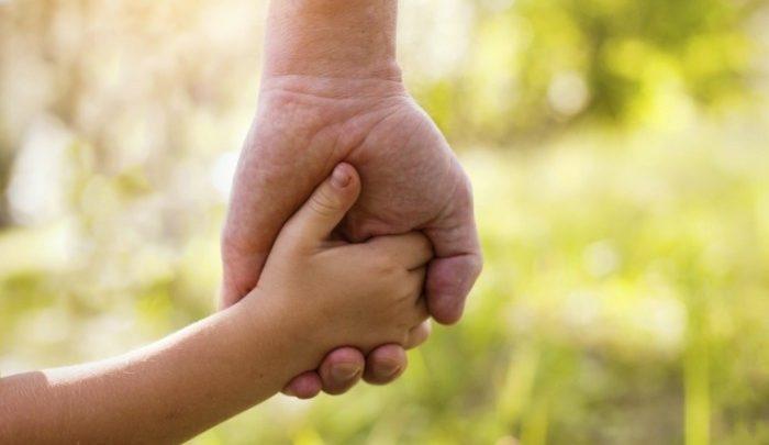 ребенок держит за руку мужчину