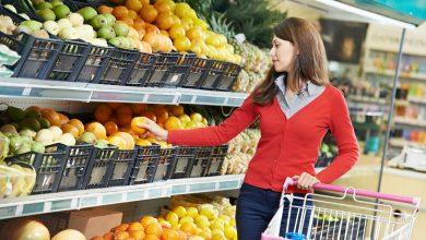 девушка выбирает фрукты в магазине