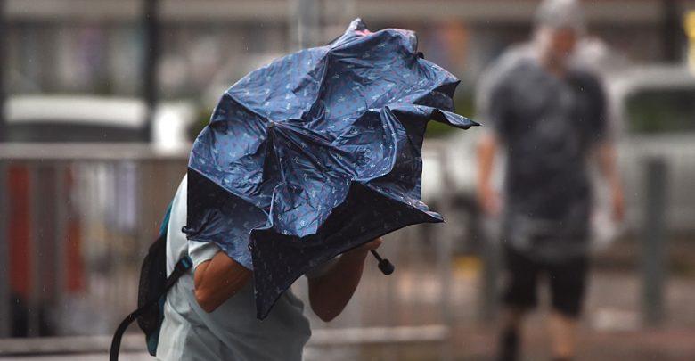сильный ветер, человек под зонтом