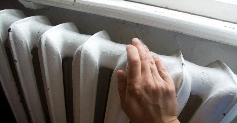 человек трогает радиатор
