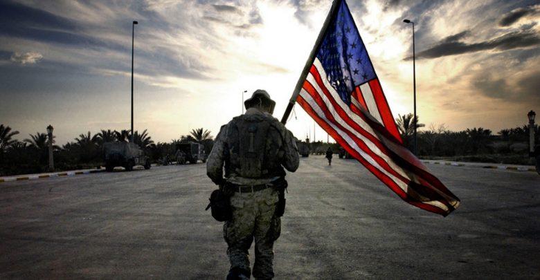 американский военный несёт в руках флаг сша