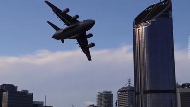 Самолёт пролетает между зданий