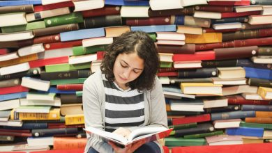 Девушка читает посреди большого количества книг