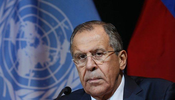 Глава МИД России Лавров на фоне флага ООН и России