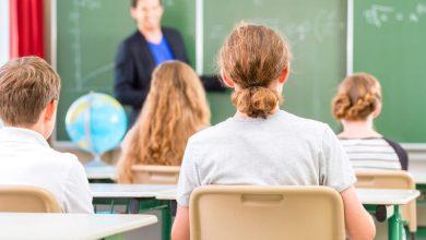 Школьник за партой на фоне учителя