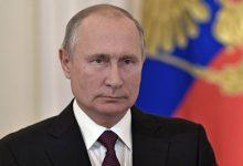 Президент России Владимир Путин на фоне государственного флага и герба России