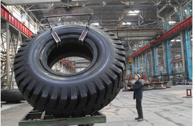 Работник завода Белашина осуществлет погрузку колёсной резины для Белаза