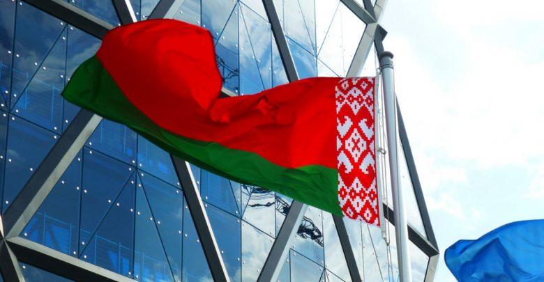 флаг Беларуси развивается на фоне высотного здания