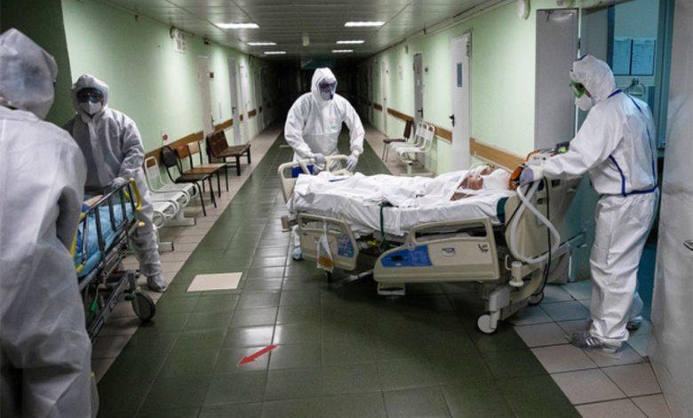 Врачи в противочумных костюмах выкатывают каталку с пациентом