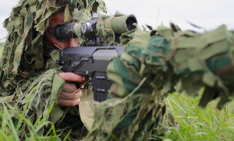 Снайпер в камуфляже смотрит в прицел винтовки